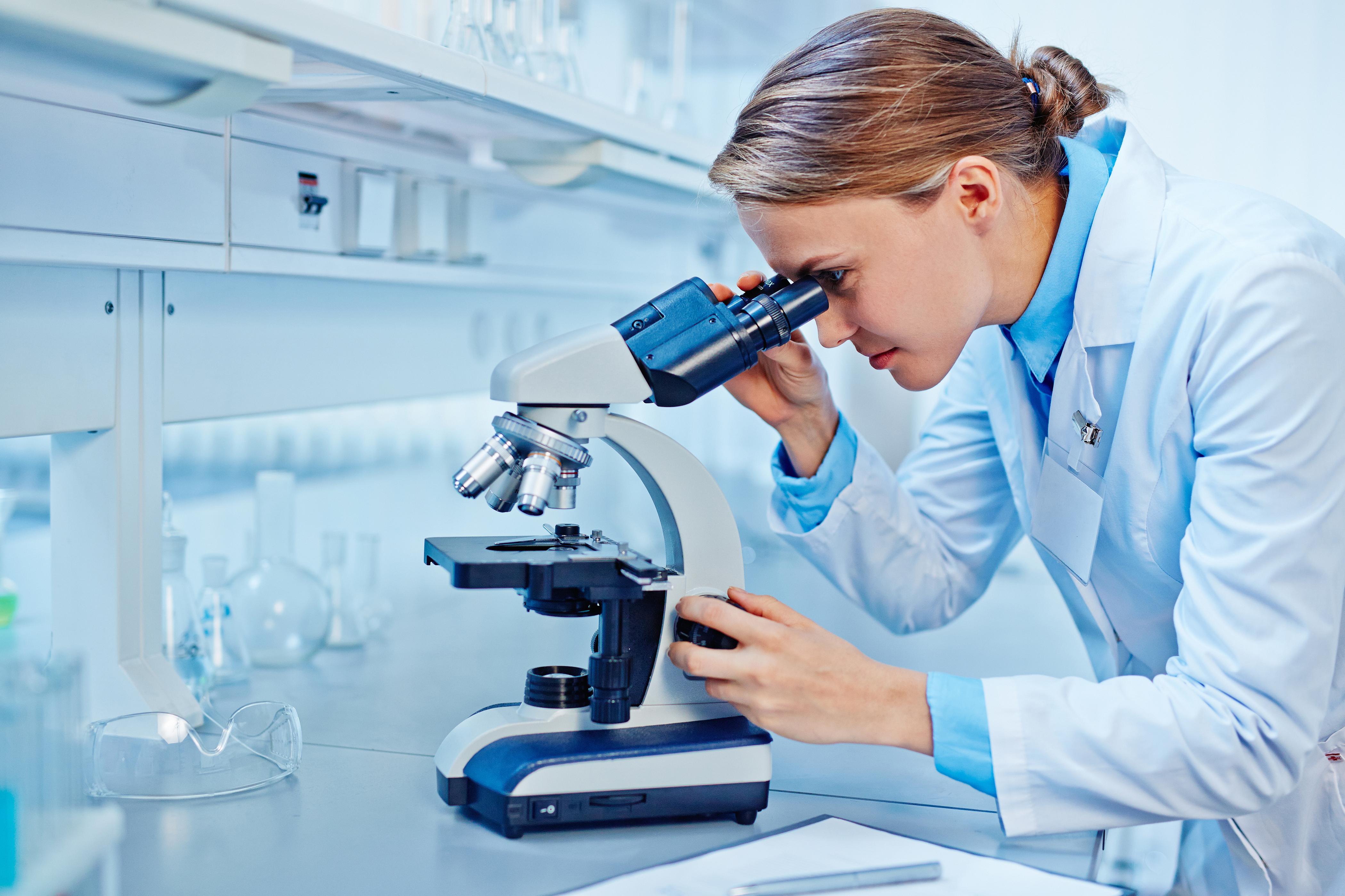 Diabetes Illustrasjonsbilde av en kvinnelig forsker som ser inn i et mikroskop